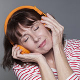 Serene mature woman smiling with headphone on for relaxation Royalty Free Stock Photo