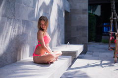 Serene meditating woman relaxing at luxury travel holiday vacation resort. Happy blissful young woman in bikini in Stock Image