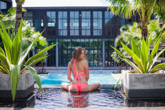 Serene meditating woman relaxing at luxury travel holiday vacation resort. Happy blissful young woman in bikini in Stock Photography