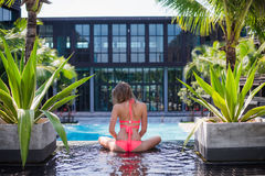 Serene meditating woman relaxing at luxury travel holiday vacation resort. Happy blissful young woman in bikini in Royalty Free Stock Photos