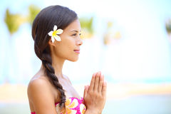 Serene meditation - meditating woman on beach. Smiling happy in profile on hawaiian beach. Beautiful portrait of mixed race Asian / Caucasian female model Royalty Free Stock Photography
