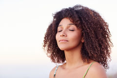 Serene mixed race woman with her eyes closed outdoors Stock Photo