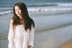 Serene moment. Portrait of beautiful Asian girl standing on serene beach Stock Image