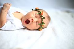 Serene newborn baby on a bed yawning. Portrait-serene newborn baby on a bed yawning.the photo has a empty space for your text Stock Photos