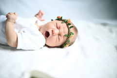Serene newborn baby on a bed yawning Royalty Free Stock Photography