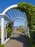 Serene passage to the shore. White arch decorated with ivy and flowers framing passage to ocean shore Stock Photo