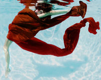 Serene passion. Woman submerged with red fabric under water Stock Images