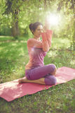 Serene and peaceful woman practicing mindful  awareness by meditating in nature with sun flare. Portrait of beautiful mixed race caucasian, african, middle Stock Photos
