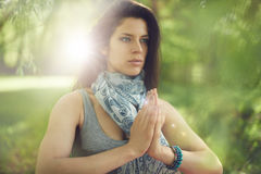 Serene and peaceful woman practicing mindful  awareness by meditating in nature with sun flare. Portrait of beautiful mixed race caucasian, african, middle Royalty Free Stock Images