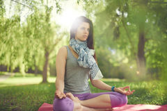 Serene and peaceful woman practicing mindful  awareness by meditating in nature with sun flare. Portrait of beautiful mixed race caucasian, african, middle Stock Images