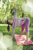 Serene and peaceful woman practicing mindful awareness by meditating in nature at sunset with background bokeh. Portrait of beautiful mixed race caucasian Stock Photo