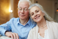 Serene pensioners. Serene senior couple leaning on one another Stock Photos