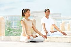 Serene People. An attractive young women and men doing yoga Stock Photo