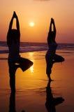 Serene People In The Beach som gör yoga i solnedgången Arkivbild