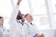 Serene physician sitting during meeting in clinic Stock Images