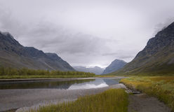 Serene river scenery in mist atmosphere streaming in between rapadalen mountain valley Stock Image