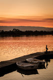 Serene. Row boats at lake pier in the sunset Stock Image