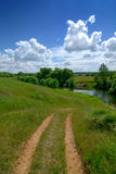 Serene rural landscape. Road river and clear sky Stock Photography