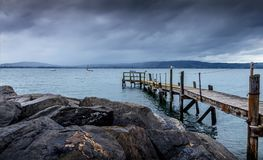 Serene Wooden Pier in Blue Waters after the Storm, Holywood, Northern Ireland. Serene and Rustic Wooden Pier in Blue Still Waters after Dramatic Storm, Holywood stock photo