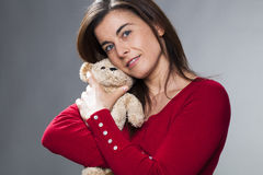 Serene 30s girl using the symbol of childhood for baby announcement. Childhood and tenderness concept - smiling young brunette woman holding teddy bear next to Stock Image