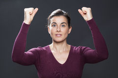 Serene 30s woman glowing from within with hands up royalty free stock photography