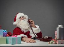 Santa Claus on the phone. Serene Santa Claus answering phone calls on Christmas Eve and preparing gifts, he is holding the receiver and listening stock photography