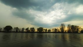 Serene savage scene. A light wind ruffled the water and stormy clouds fly away over the trees on riverbank. Sundown. stock video footage