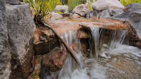 Serene scene of water flowing over rocks in the garden stock video footage