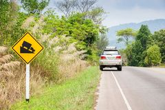 Serene scenery along the mountain road to Thailand-Cambodia border. Trat Province, warning sign foreground, focus on silver SVU car parking on the roadside royalty free stock photos