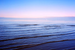 Serene sea. Serene Baltic sea with tiny waves and a sail in far background Stock Images