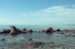 Serene seascape with rocks in the foreground and boat on horizon Royalty Free Stock Photo