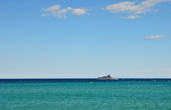 Serene seascape with yacht on the horizon. Seascape with yacht on the horizon in Saint-Tropez on a clear summer day Stock Photo