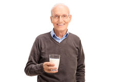 Serene senior gentleman holding a glass of milk Stock Photography