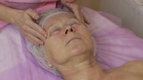 Rejuvenating facial contour massage in spa salon. Serene senior woman lying on the table with eyes closed enjoying facial spa treatment in beauty salon. Closeup stock video