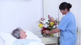 Serene senior woman speaking at a nurse who gives a bouquet of flowers stock video footage