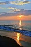 Serene and Shining Summer Seashore Sunrise. A serene summer seashore sunrise with glowing and glistening seas and shining sands on the beach Royalty Free Stock Photos