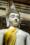 Serene smiling statue of a Buddha, Thailand. Ancient sculpture of a buddha in yellow robes. Temples and pagodas in Ayutthaia, ancient capital of Thai kingdoms Royalty Free Stock Photography