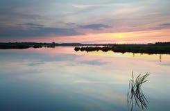 Serene summer sunset on lake Stock Images