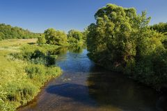 Serene sunny summer landscape. Small river with green meadows an Royalty Free Stock Photography
