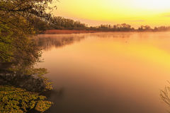 Serene Sunrise at the Lake. Spring Dawn. Lovely colors. Tree Silhouettes and warm water in Bavaria, Germany Royalty Free Stock Photos