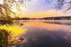 Serene Sunrise at the Lake. Spring Dawn. Lovely colors. Tree Silhouettes and warm water in Bavaria, Germany Royalty Free Stock Images