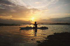 Serene sunset in the lake and boatman Stock Image