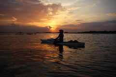 Serene sunset in the lake and boatman Stock Images