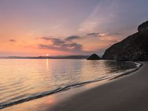 Serene Sunset, Polkerris Beach, Cornwall. Serene Sunset with sun dipping on the horizon, Polkerris beach, Cornwall royalty free stock images