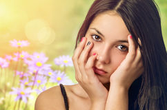 Serene Teenager. Beautiful serene teenage girl with hands on face over spring flowery background Stock Photo