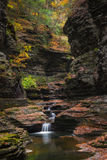 Serene waterfalls and natural pool. Fall colors surround a beautiful little waterfall and natural pool at Watkins Glen New York Royalty Free Stock Photography