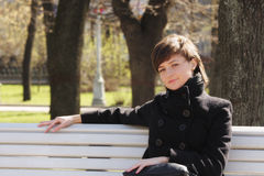 Serene woman in black on bench. Young serene woman in black overcoat sitting on bench Stock Photos