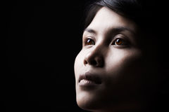 Serene woman in dark. A close up portrait of serene woman in dark Stock Image