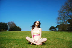 Serene woman in field. A beautiful young serene woman sitting in a field with a blue sky stock image