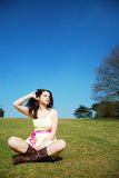 Serene woman in field. A beautiful young serene woman sitting in a field with a blue sky stock photography